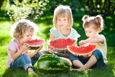 Group of happy children eating watermelon outdoors in spring park