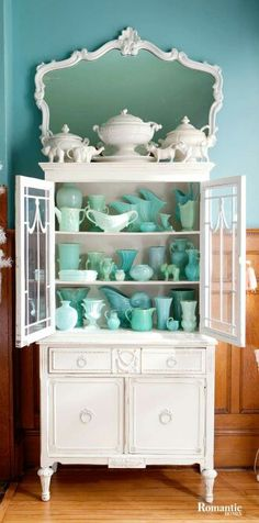 Turquoise milk glass & white pottery collection. Love the way the mirror completes the design! (Romantic Homes magazine)