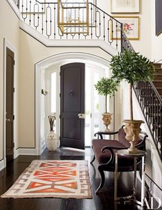 Custom-made moldings amplify the elegance of the entrance hall, which contains a Regency settee and a 1920s Navajo rug | http://archdigest.com