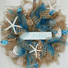 """22"""" in Diameter Burlap and Teal Deco Mesh wreath accented with several types of ribbon (Teal, Tan, and White) along with three Starfish and 3 Sand-dollars. sign is optional."""