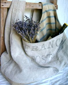 "This sling bag has been constructed from a beautiful, antique French postal sack. It is fully lined with vintage blue and tan linen ticking  Measures approx: 26.5"" x 17.5"