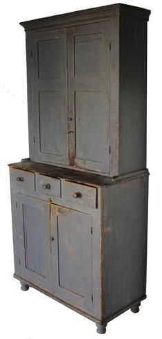 19th century two piece stepback Cupboard with original gray paint two panel doors over three dovetailed  drawers, with wooden turned knobs, over two panel doors below. Resting on very gracefully turned feet, applied cove molding, beautiful wear to the paint,Circa 1840 - from Country Treasures