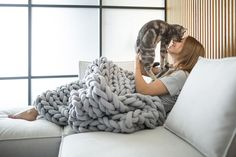 Two of your best companions: a cozy blanket and a lovely cat!