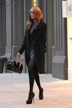 Tyra Banks in a gray dress and a long winter coat in NYC.
