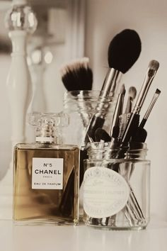Vanity vignette with apothecary jars used to house makeup brushes and Chanel No. 5.