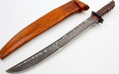 "This Mick Strider custom short sword features a ""Nightmare"" ground damascus blade with a false top edge. Blade flats have a rough or hammered like finish. Damascus guard and a grooved brown canvas micarta handle that feels great in the hand. Tang is visible on spine of handle only and goes half the length of the handle. 5/16"" blade stock and 1 5/8"" blade depth. Inlcudes a brown leather sheath."