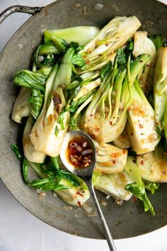 Sauteed baby bok choy fully cooked in an old heavy wok sprinkled with crushed red chili flakes.