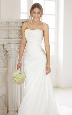 Stella York - Style 5702 This amazing strapless Satin Chiffon wedding gown is crafted with an asymmetrical figure-flattering ruched waist and beautiful beaded appliqué at the hip.
