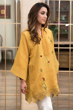 A mustard khadar shirt, embellished with laces and hand embroidered botanical motifs. Silk Dress Design, Fancy Dress Design, Dress Neck Designs, Designs For Dresses, Simple Pakistani Dresses, Pakistani Fashion Casual, Pakistani Dress Design, Pakistani Outfits, Embroidery Suits Design