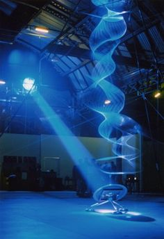 "Physicist & artist Paul Friedlander produces interactive kinetic light sculptures by quickly rotating a rope stretched from ceiling to floor through white light. The vibrating string becomes invisible, but the white light that's being reflected off the rope becomes visible: ""The sculpture is an example of the use of my invention chromastrobic light, light that changes colour faster than the eye can see... images are digitally processed in real time using custom software."""