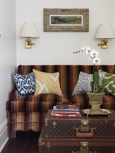 Amazing living room with baroque frame flanked by antique brass swing-arm sconces over colorful velvet striped sofa with brass nailhead trim filled with blue ikat pillow, yellow ikat pillow and green ikat pillow paired withs tacked Louis Vuitton Trunks.