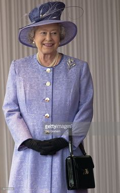 Queen Elizabeth Ll Smiling During The State Visit Of The American President At Buckingham Palace. The Queen Is Wearing A Mauve Coat With Matching Hat Which She Has Accessorized With Black Gloves And A Black Launer Handbag.