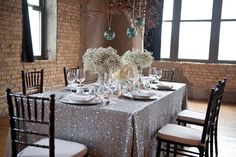 Centerpieces From the glittering tablecloth to the dangling ornaments, this table display is a winter dream.