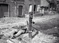 An American soldier lies dead beside water pump, killed by a German booby trap set in the pump in a French village on the Cherbourg Peninsula, on June 18, 1944.