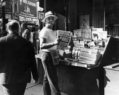 A news stand operator smokes a cigarette at his kiosk while holding a copy of the 'New York Post,' which bears the headline, 'PARIS FREED!,' New York City, World War II.