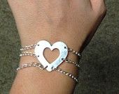 Simply dramatic this beautiful heart bracelet with three strands is a sure show stopper. This bracelet will go beautifully with anything from a pair of jeans to a cocktail dress!    Made of sterling silver the strands are only connected to the heart charm. Each strand must be individually clasped with a fish hook clasp, preserving the dramatic design.  Fits wrist size 7-7.5.  EBay: http://www.ebay.com/itm/321751296149?ssPageName=STRK%3AMESELX%3AIT&_trksid=p3984.m1555.l2649