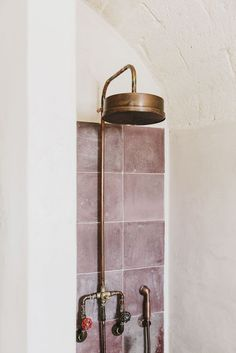Pink tile shower with copper faucet fixtures.