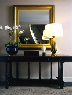 Matte gold mirror and lamp paired with high gloss black console adds drama and reflects light in your entry!