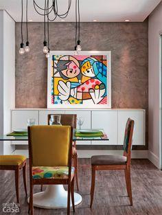 A parede da sala de jantar deste apartamento recebeu cimento queimado comum com uma demão de resina sintética. O tampo de vidro incolor leva adesivo vinílico na face de baixo. Projeto de Cecília Guerra e Cristiane Tamburri. #dining