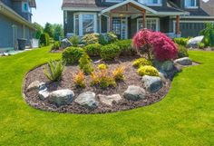 Nicely decorated landscaped colorful flowerbed with flowers, stones and bushes