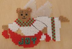 "Perler Hama fuse bead teddy angel:    The wording ""JOY"" looks funny because I put glitter on it. I used paint to add the mouth, ..."