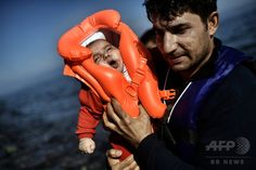 A migrant holds a baby as refugees and migrants arrive at the Greek island of Lesbos after crossing the Aegean sea from Turkey on October 5, 2015. (c)AFP/ARIS MESSINIS
