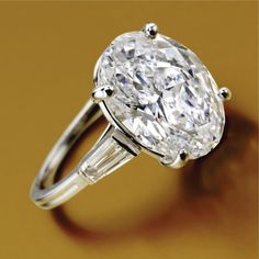 DIAMOND RING, TIFFANY & CO The oval modified brilliant-cut diamond weighing 7.33 carats, flanked by 2 tapered baguette diamonds, mounted in platinum, size 6¾, signed Tiffany & Co.