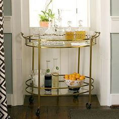 gold cart, seafoam walls, white trim, graphic fabric.