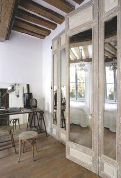 Dans la chambre, le grand placard a été habillé de portes anciennes chinées recouvertes de miroirs. Bureau, tabouret, lampe chinés aux Puces.
