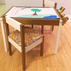 Our Ikea Latt hack art table! Vinyl upholstered seats, chalkboard top, roll of art paper mounted underneath.