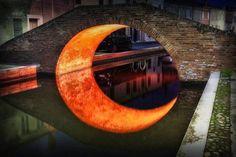 Just a moon underneath a bridge