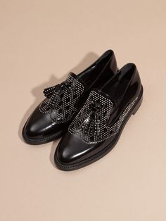 Burberry leather loafers adorned with tassels and polished studs in a wingtip design - a striking counterpoint to tailored trousers, or a floaty silk dress.