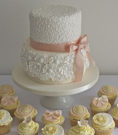 White wedding cake with peach bow and cupcakes.