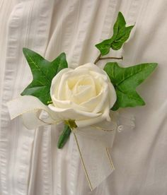A single artificial wedding buttonhole,with a   lovely ivory diamantie rose, light catching crystals,  a spray of ivy leaves and a ivory sheer organza bow   with a gold edge.     A pin will also be included.    Guest buttonholes or boutonniere's are a great   memento and keepsake for your wedding guests.  Whether you choose to give every single guest a   buttonhole or just close family and friends.  This is also, an ideal job to delegate to one   of your wedding ushers on your big day.