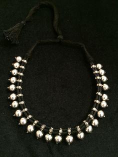 Collar con bolitas de plata y cordón de algodón en color negro con cierre corredizo. www.litticomplementos.com
