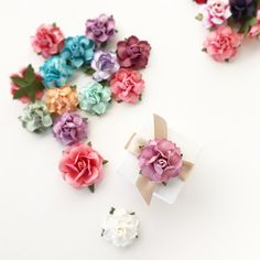 "Our most popular DIY supply! Sturdy paper flowers measure 1.5"" across, and come in 22 custom colors. Perfect for DIY wedding & craft projects."