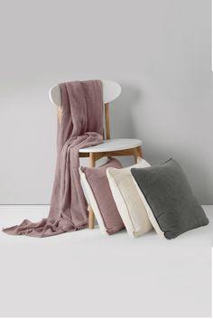 Kati Leinendecke in Flieder und Leinenkissen in Flieder, Stahlgrau und Mattweiß. Kati wurde aus Leinen gewebt, weshalb die Decke leicht strukturiert ist. Stoffe aus der robusten Naturfaser verleihen deinem Sofa zudem eine weitere Textur.