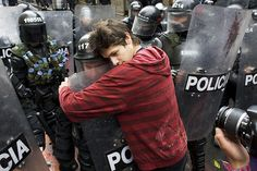 A protester hugging a riot police officer in Bogota, Columbia.
