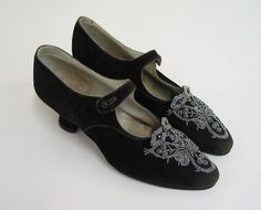 1915; Shoes; black suede strapped with beaded design on toe. Black suede uppers. Toe is pointed with a beaded design from tip to throat line. Strap across instep secures with a button. Lined in white leather. Covered 1-1/2 inch Louis style heel.