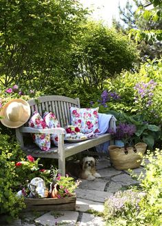 Bench in flower garden with pretty floral pillows. Robin Stubbert Photographer - Garden Photography