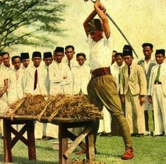 Officer of the Imperial guard demonstrating the katana sword cutting power to Malaysian civilians (Singapore 1942)