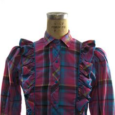 Awesome vintage 1980s button up western inspired shirt with cute ruffles up the front & back. Plaid print in hot pink & turquoise. Snaps up the