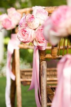 Clusters of roses affixed to chairs down the aisle (repurposed on reception tables after ceremony)