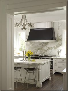 marble does make a beautiful wall. i like the black and steel contemporary hood and bertoia bar stools at the island