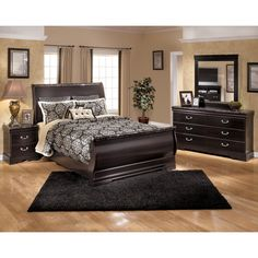 The Esmeralda sleight bed from Ashley Furniture showcases a luxurious sleigh design with elegant faux marble tipping the head and footboard, highlighted by the rich dark merlot finish over beautiful replicated mahogany wood grain.