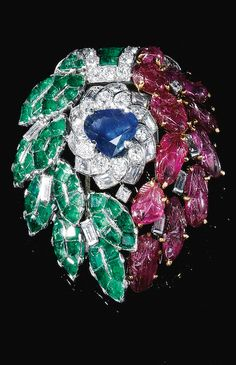 GEM SET AND DIAMOND BROOCH Designed as cascading leaves set with carved rubies, calibré-cut emeralds and a triangular sapphire, accented with circular-cut and baguette diamonds, French import marks.