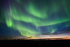 Curtains of Aurora Borealis - Northern Lights - over an Alaska sunset. © iStockphoto / Roman Krochuk