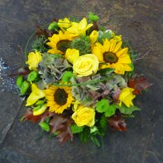 Small funeral #Posy flower arrangement in yellow #Sunflowers, #Roses and #Freesias, #AutumnalLeaves and #Hydrangeas, and green #Chrysanthemums, with looped #grasses. Florist London, Funeral Tributes, Same Day Flower Delivery, Flower Arrangements, Posy Flower, Floral Wreath, Chrysanthemums, Florists, Wreaths