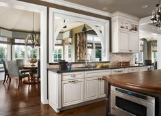 A grand traditional style kitchen design with white Dura Supreme Cabinetry and an arched look-through to the dining room space. Kitchen And Bath, New Kitchen, Kitchen Ideas, Kitchen Pass, Kitchen Island, Kitchen Cabinets, Traditional Style Kitchen Design, Supreme, Kitchen Stories
