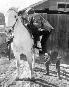 """Barbara (Bobbi) Ohlhoff, a 24-year-old nurse from New York, gets a boost onto a horse from an 8-year-old cowboy, David. Bobbi and her sister, Anita, were venturing across the country to San Francisco in March 1963. While in Nebraska, they stopped at Y Lazy Y Ranch in Box Elder Canyon, where the pair saw their first cows, steers and calves. """"This has just been perfect,"""" Bobbi said. """"We just can't get over how friendly and concerned everybody is in Nebraska to perfect strangers."""" THE WORLD-HERALD"""